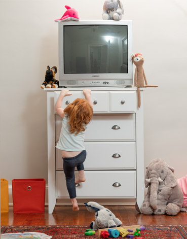 Child climbing on dresser with CRT TV perched on top
