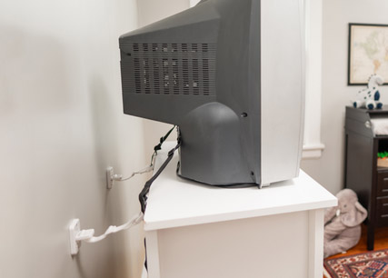 CRT TV attached to wall with two brackets and straps