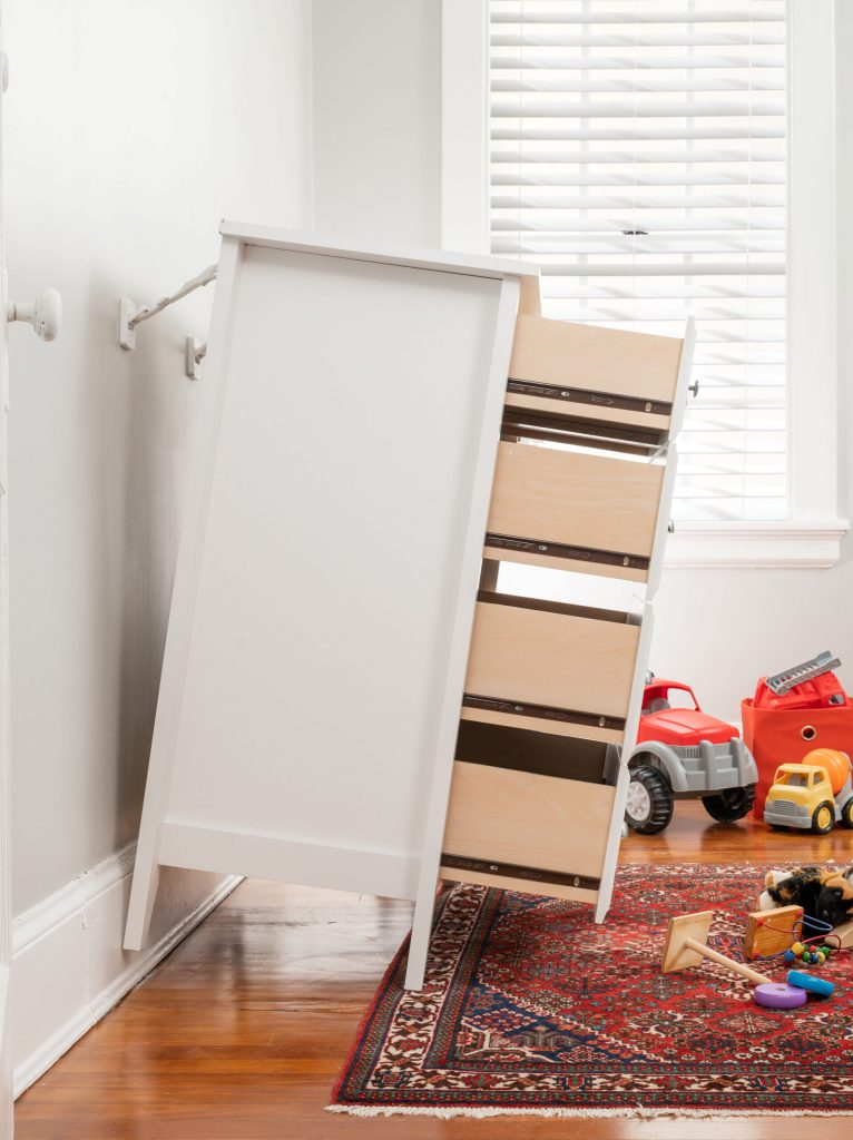 Anchored dresser tipping away from wall but not falling